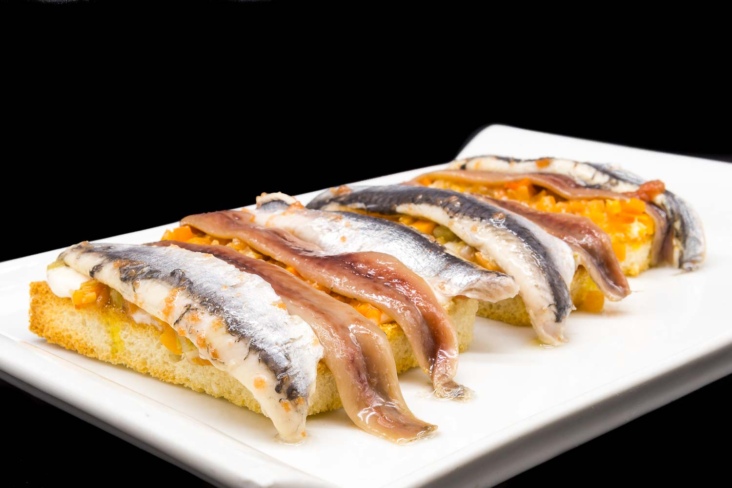 Toasts of anchovies and sardines on vegetables