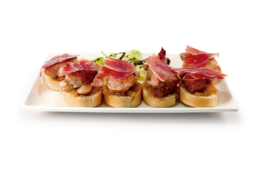Grilled pork medallions with Iberian ham over toast